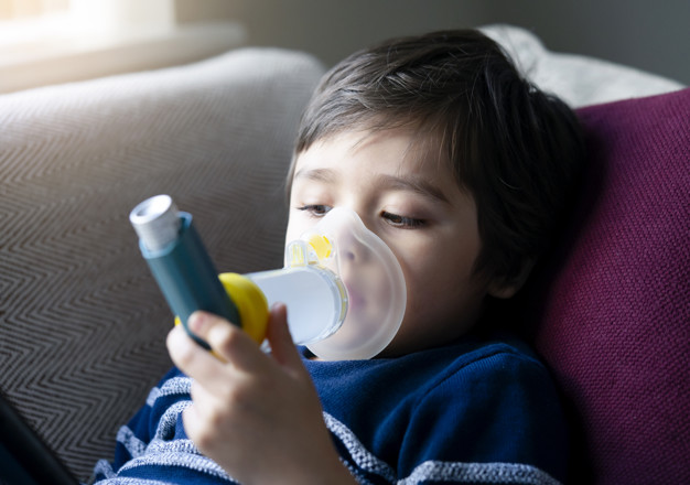 Close up kid face using volumtic for breathing treatment,Poor boy have a problem with chest coughing holding inhaler mask,  Child having asthma allergy using the asthma inhaler, Healthcare concept
